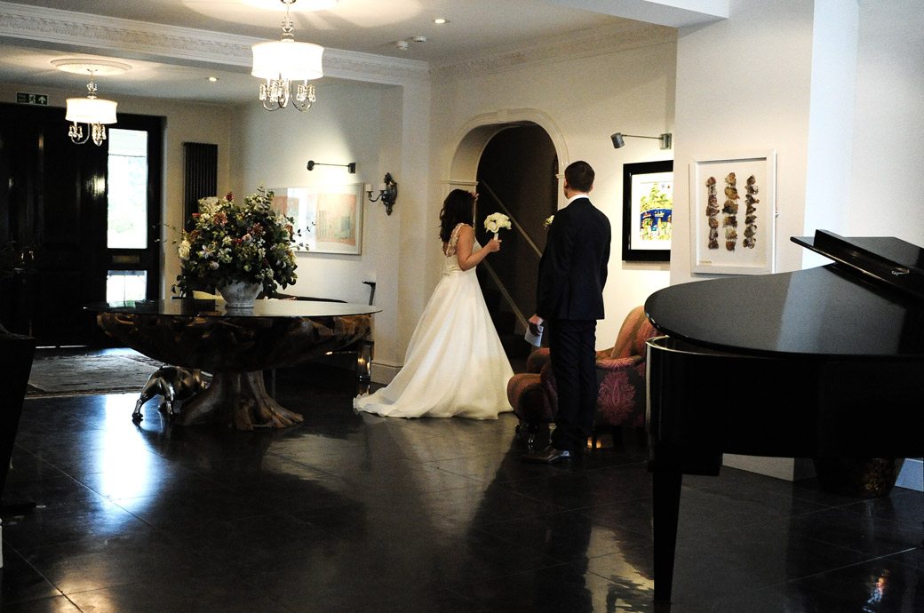 Groom looks on by the grand piano as his Bride checks her hair in the hall mirror in this wedding photograph taken in the village of Chiddingfold Surrey at Russets Country House