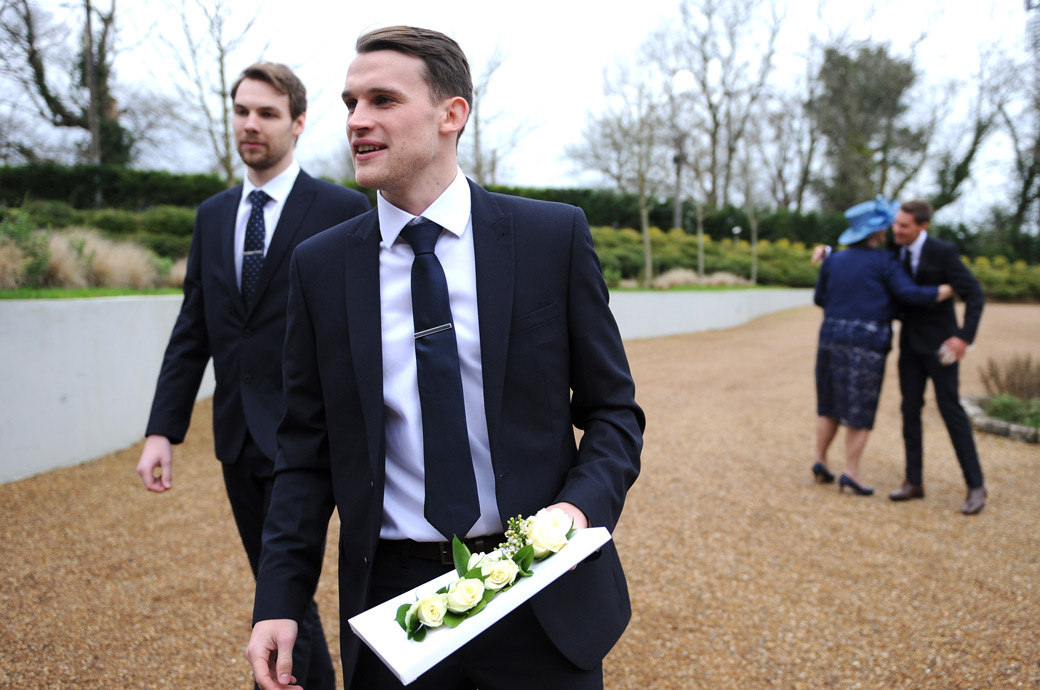 Wedding picture of a Groomsman on the gravel drive of the lovely Surrey wedding venue Russets Country House in the village of Chiddingfold with the buttonholes