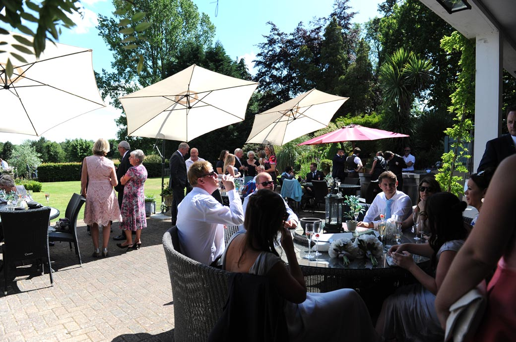 Guests relaxing over drinks under the patio umbrellas as the wedding reception gets into swing at the stunning wedding venue Russets Country House in Surrey