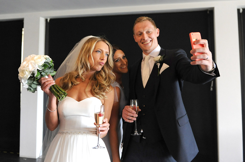 Wedding picture of the Bride and groom posing for the ubiquitous selfie as they drink champagne on arrival at the lovely Surrey wedding venue Russets Country House in Godalming