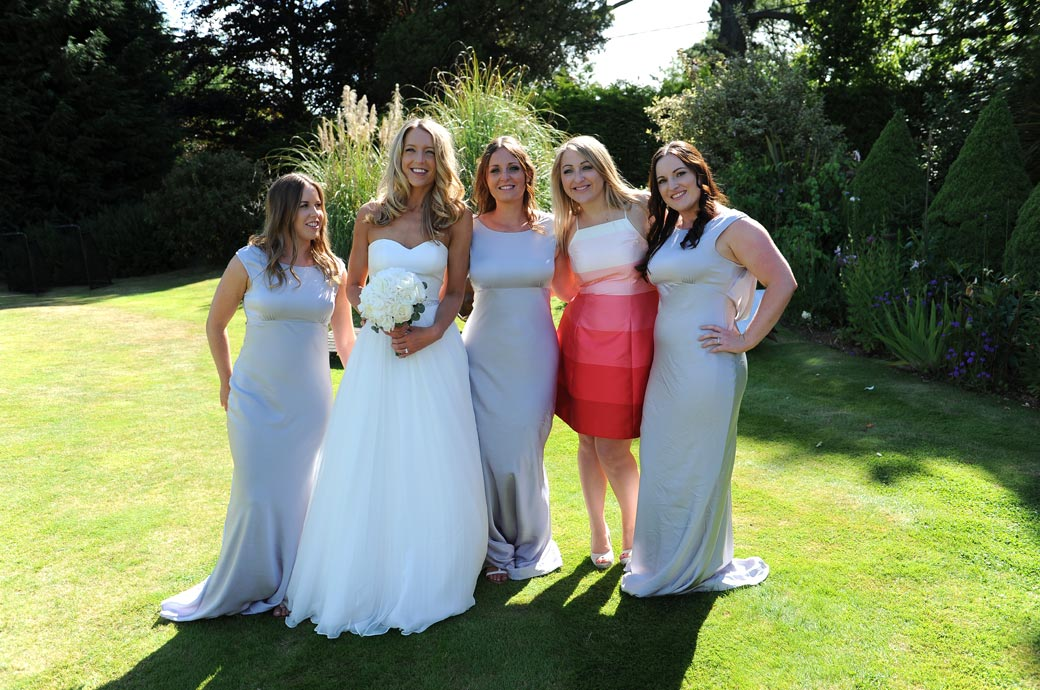 Informal wedding photo of the bride posing with a friend and bridesmaids in the lovely gardens at Russets Country House a beautiful and popular wedding venue in Surrey