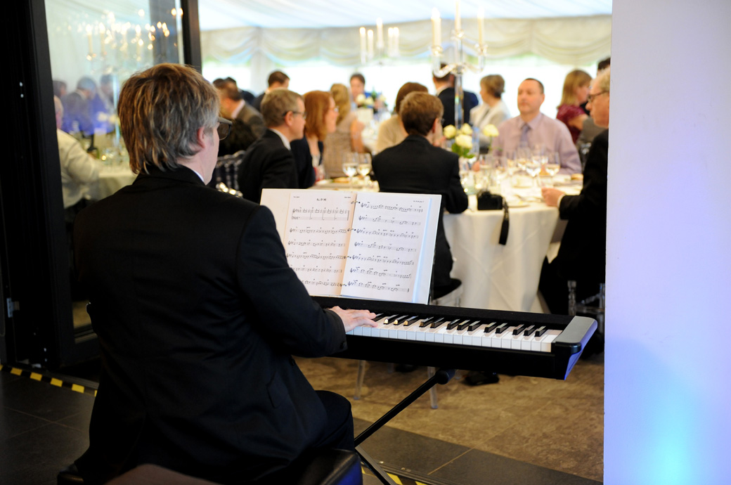 Wedding photo of a musician playing music during the wedding breakfast at the fabulous Russets Country House captured by Surrey Lane wedding photographers