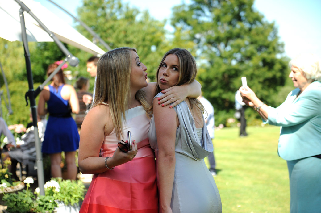 Bridesmaid and friend caught in this fun wedding picture as they pout for a guest's camera in Surrey wedding venue Russets Country House lovely landscaped gardens