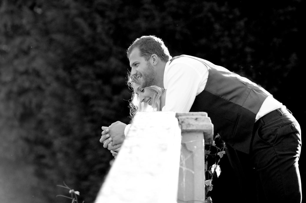 A relaxed wedding photograph of a couple leaning over a balustrade in the gardens at Surrey wedding venue Russets Country House watching the fun and antics below