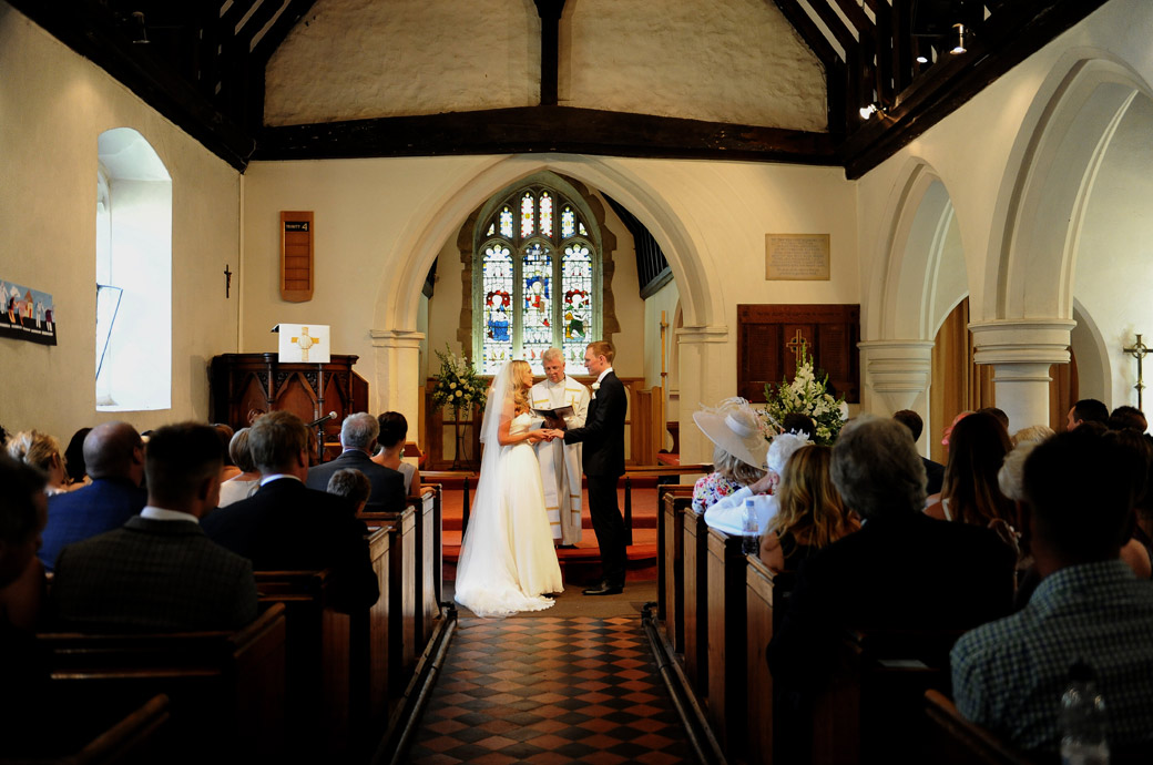 Bride and Groom down the church aisle saying their marriage vows before they leave for the delightful wedding venue Russets Country House  in the Surrey Hills
