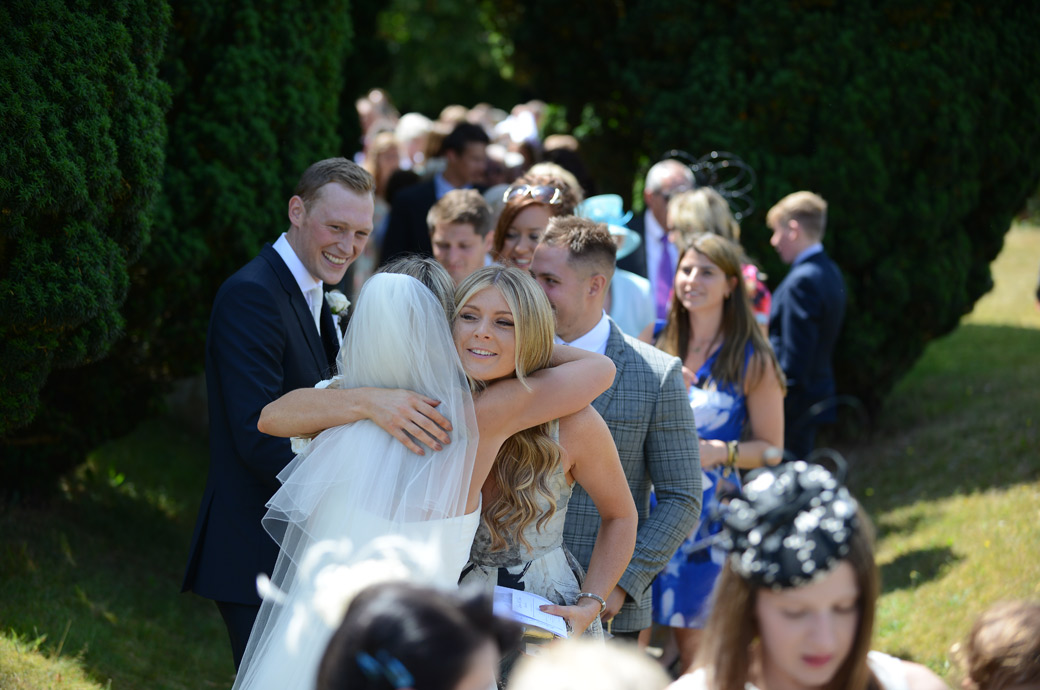 Bride being hugged by a friend in a church receiving line while her Groom looks on prior to leaving for Russets Country House  captured by Surrey Lane wedding photographers