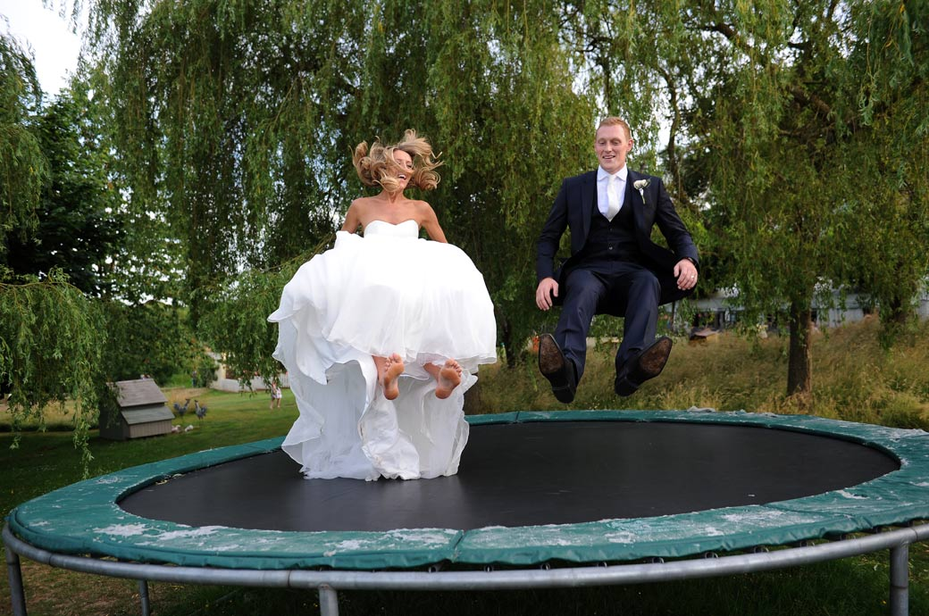 Hilarious and unusual wedding photo of the Bride and groom having fun at Surrey wedding venue Russets Country House as they bounce in perfect union on a trampoline