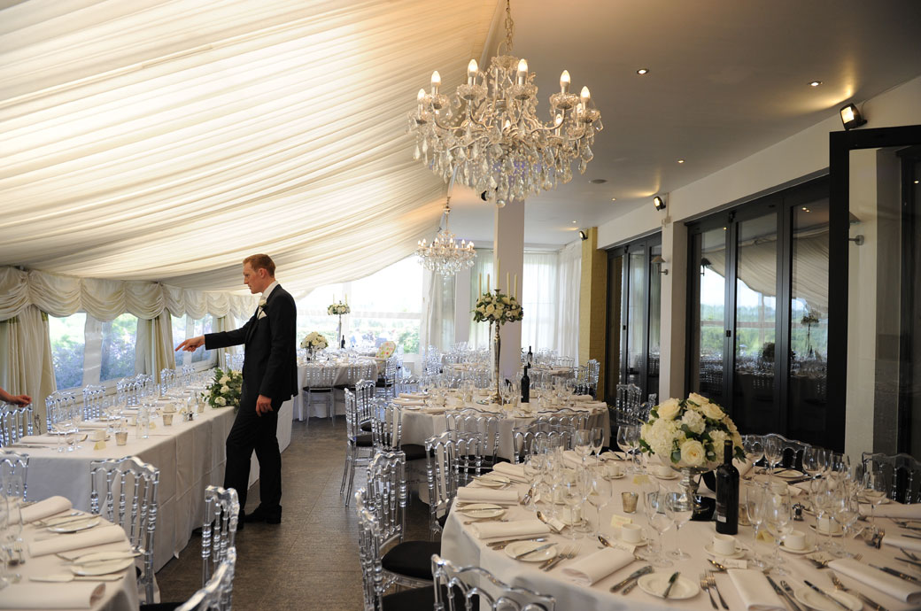 Groom inspecting the wedding breakfast settings on the head table in the beautifully rich and classic looking dining room at a Russets Country House wedding reception