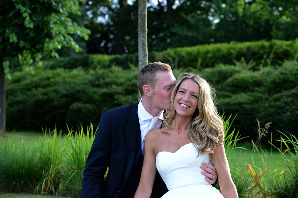 The groom kisses his happy smiling Bride in this wedding photo taken at the front of the lovely Surrey wedding venue Russets Country House as they sit on a wall at the entrance