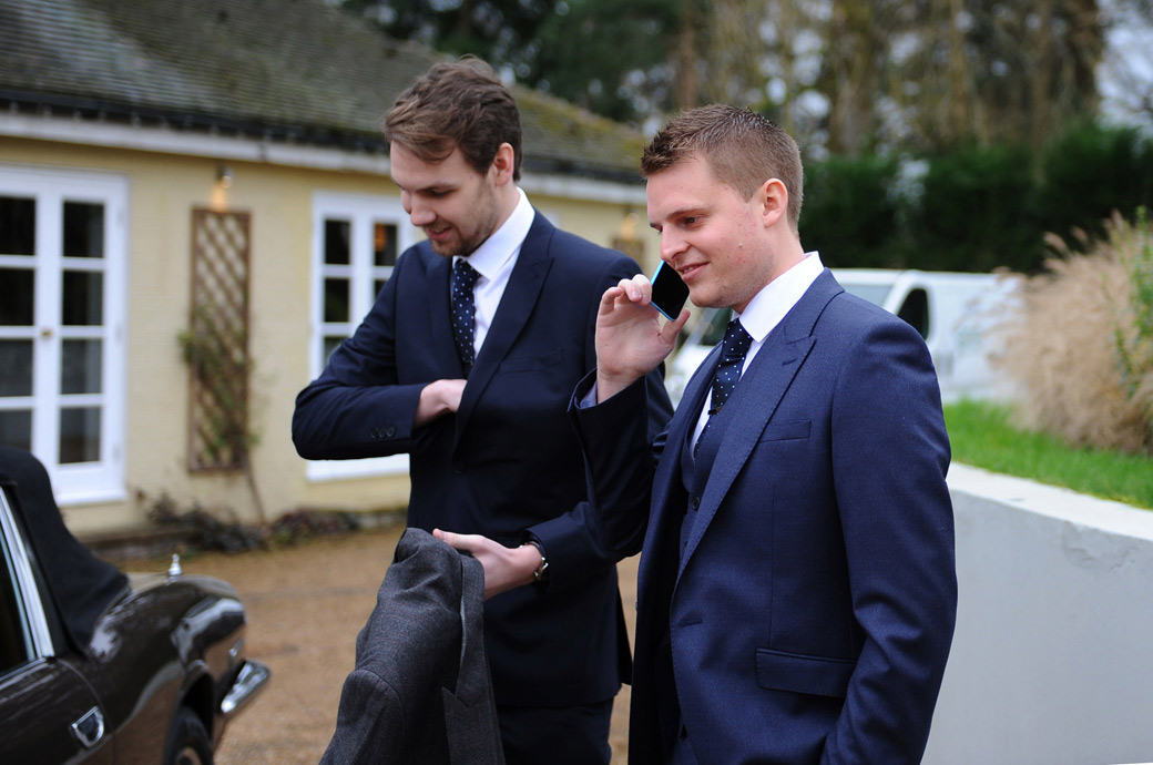 Groom on the phone with his Best man captured in this wedding photo taken outside Russets Country House in Chiddingfold Surrey as they await the arrival of the wedding guests