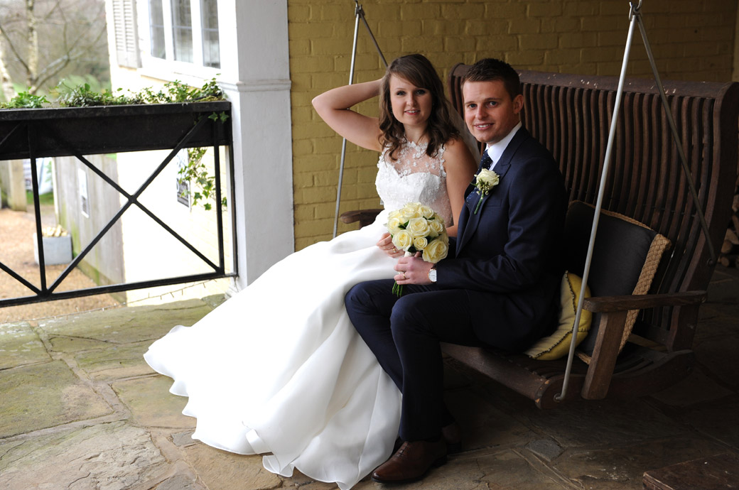Sweet wedding picture of the Bride and groom sitting on a swinging seat on the Russets Country House porch in the quaint village of Chiddingfold in Surrey