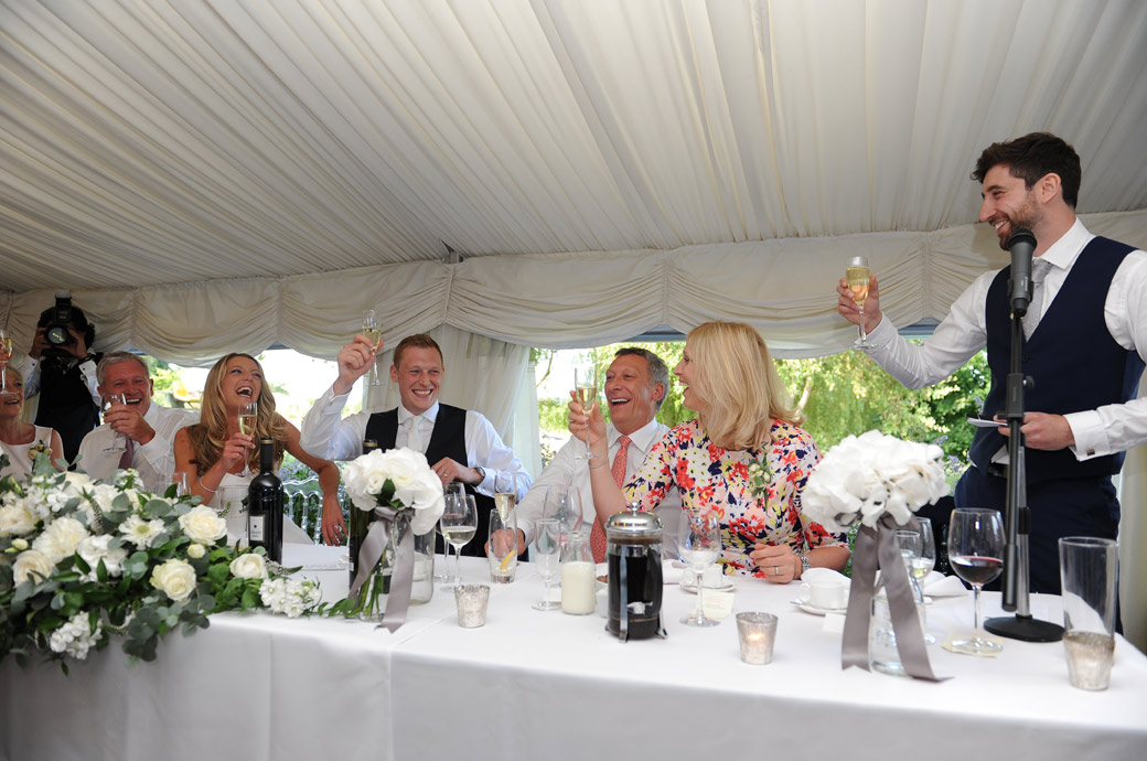 The best man raises a toast to the laughing Bride and Groom in this fun Russets Country House wedding picture captured by a Surrey Lane wedding photographer in  Chiddingfold village