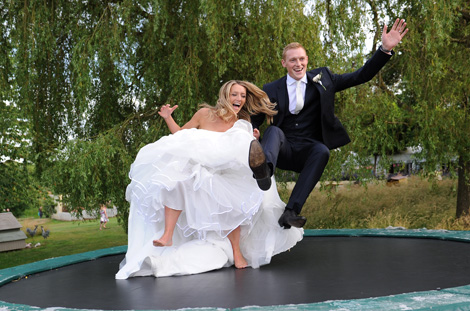Happy newlywed couple having a fabulous time as they bounce on the trampoline in this wedding picture from Russets Country House a Surrey wedding venue of note