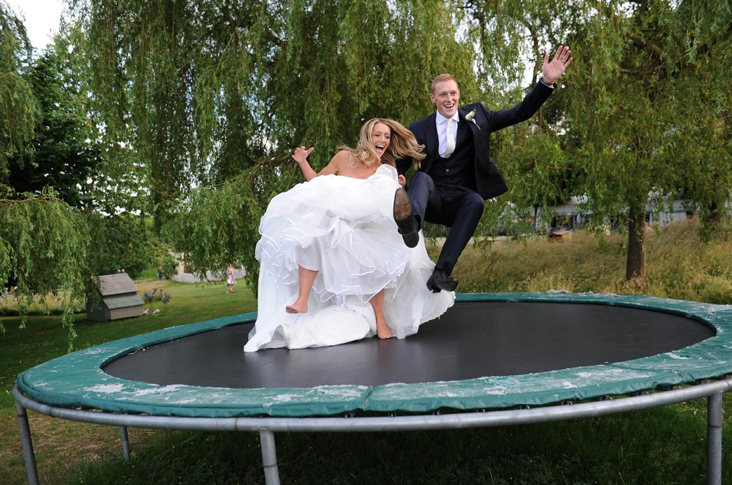 Wonderfully entertaining wedding photograph of the Bride and groom bouncing together on the Surrey wedding venue Russets Country House trampoline
