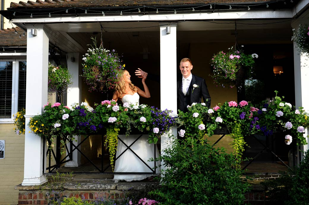 Groom plays around with his Bride in this relaxed spooky hand wedding picture taken from the Surrey wedding venue Russets Country House's colourful flower filled front porch