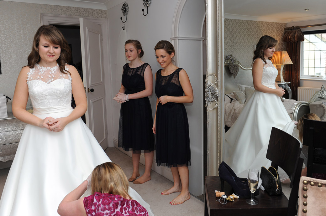Delightful wedding photo of the Bride at Russets Country House in Surrey reflected in a mirror having her dress attended to as her bridesmaids look on in the Bridal Suite