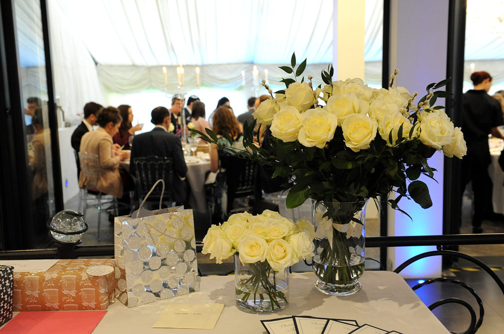 Looking past the presents and vases of yellow roses to  the guests dining at the wedding breakfast at the fabulous wedding venue Russets Country House in Chiddingfold Surrey