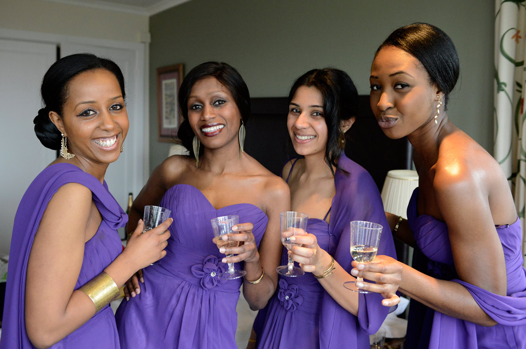 Bridesmaids in purple dresses having fun as they raise their glasses of champagne in the bridal suite at Surrey wedding venue Selsdon Park Hotel before the marriage ceremony