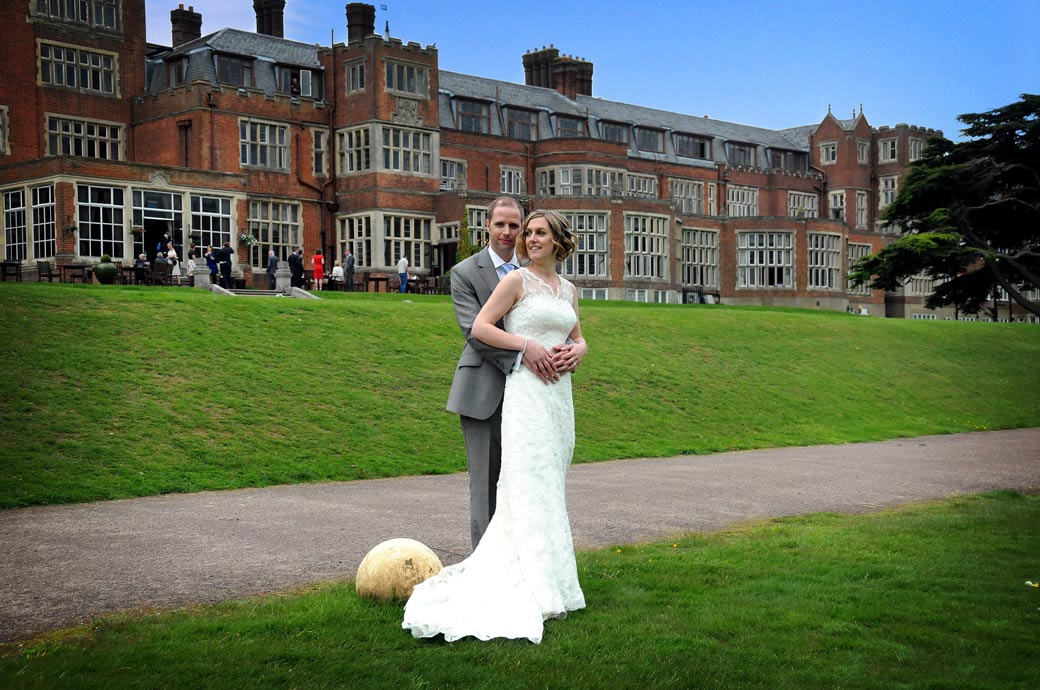 The Groom lovingly holds his wife in the grounds of Surrey wedding venue Selsdon Park Hotel in Croydon as they have time for a romantic walk before joining the wedding reception