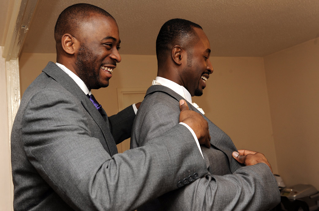Best man helps the Groom on with his jacket in this lovely fun and joyful wedding photo taken by a Surrey Lane wedding photographer at Selsdon Park Hotel, Croydon