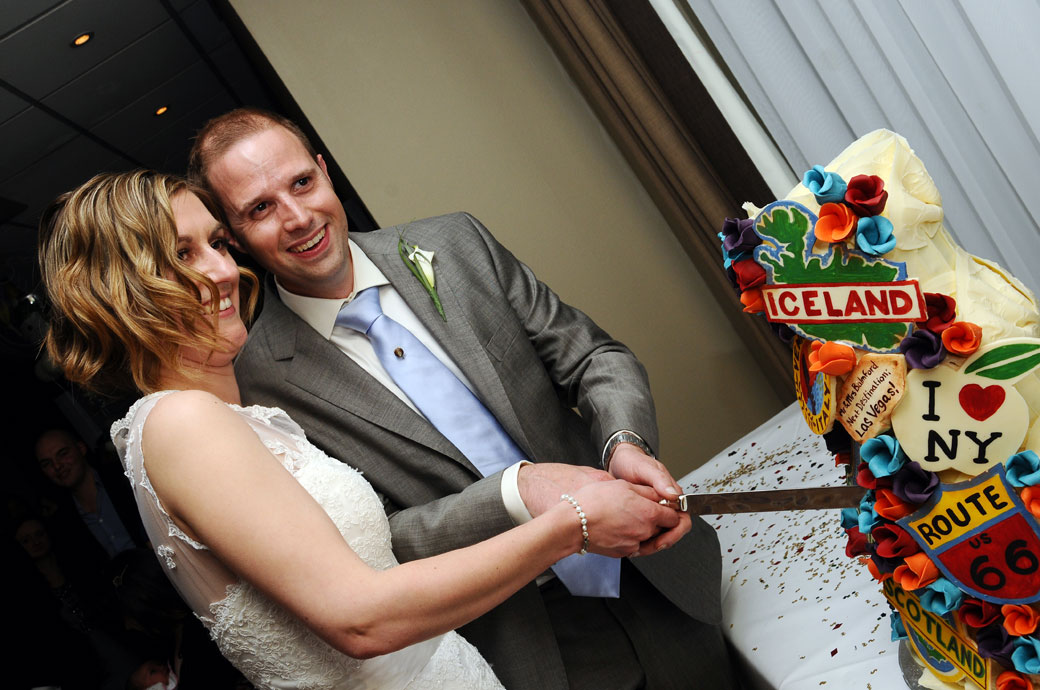 Happy mischievous looking Bride and Groom about to cut their fabulous travel themed Chockywockydoodah wedding cake at Surrey venue Selsdon Park Hotel in Croydon