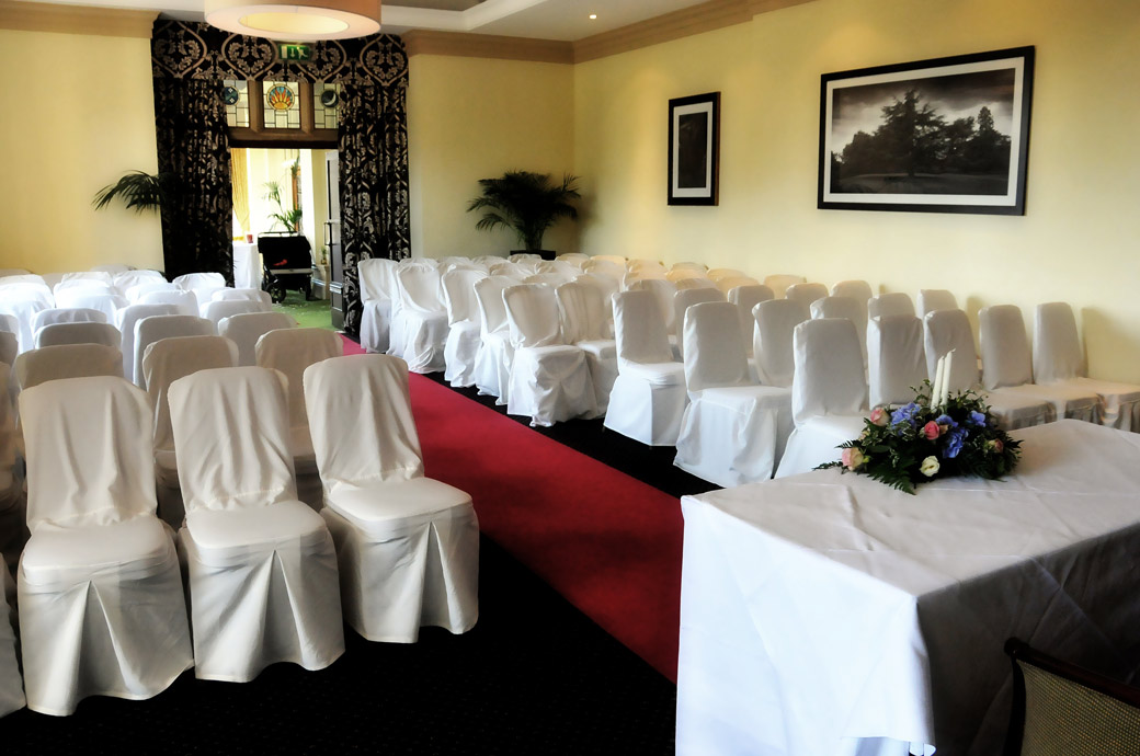 One of the popular wedding ceremony rooms at the large rambling Surrey wedding venue Selsdon Park Hotel dressed ready for the arrival of the guests and bride and groom