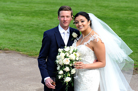 Smiling newlywed couple at the grand and rambling Surrey wedding venue Selsdon Park Hotel in Croydon as they go around the grounds for a romantic walk