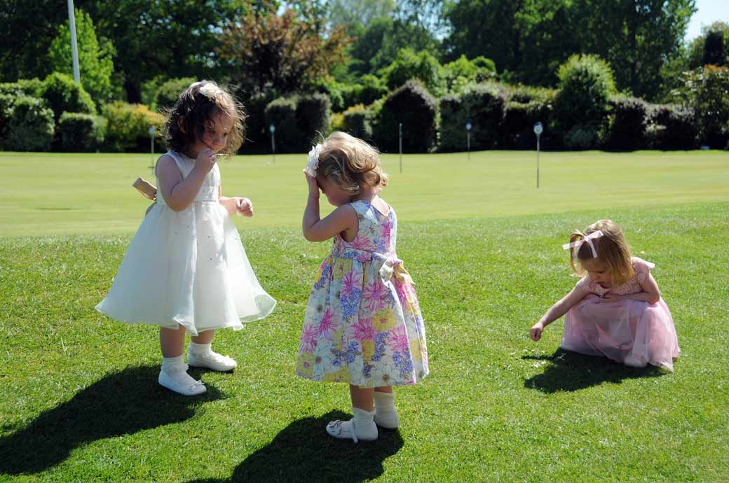 Cute little Bridesmaids playing out on the grass wedding photo captured next to the putting green at a Surrey wedding at Shirley Park Golf Club