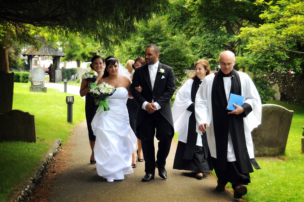 An excited and nervous Bride wedding picture taken as she walks down the path towards St. John the Evangelist Church, Old Coulsdon an ancient Surrey wedding venue