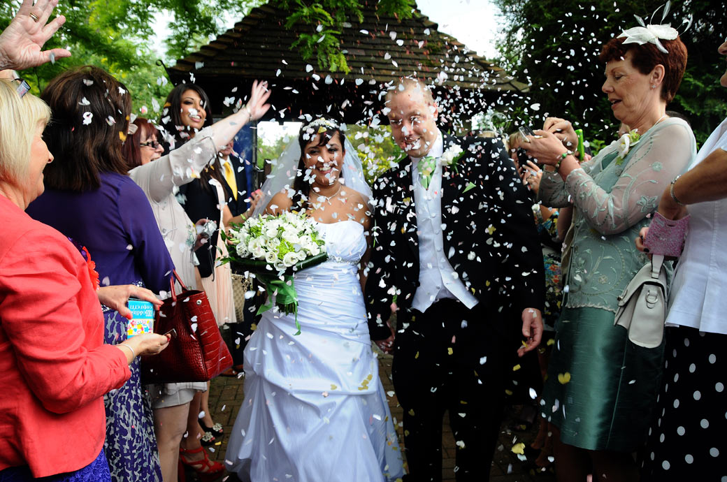 Confetti time beyond the lychgate in this fun wedding photograph captured by Surrey Lane wedding photography at St. John the Evangelist Church, Old Coulsdon