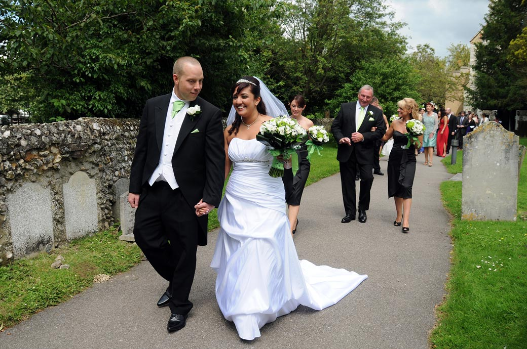 A happy Bride and Groom lead family and guests down the path in this wedding photograph taken at St. John the Evangelist Church, Old Coulsdon an old Surrey wedding venue