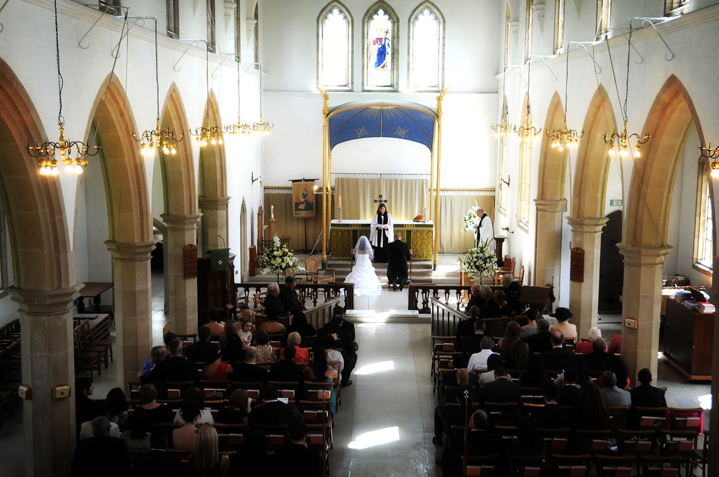 An aerial wedding picture of the Bride and Groom kneeling at the alter taken at Surrey wedding venue St. John the Evangelist Church, Old Coulsdon from the balcony