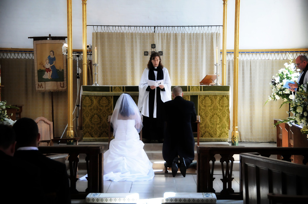 Bride and Groom kneeling down at the alter for a blessing wedding picture taken at St. John the Evangelist Church, Old Coulsdon by Surrey Lane wedding photography