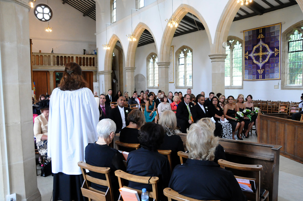 Unusual congregation wedding photo taken from behind the choir at St. John the Evangelist Church, Old Coulsdon a Surrey wedding venue dating back to the eleventh century