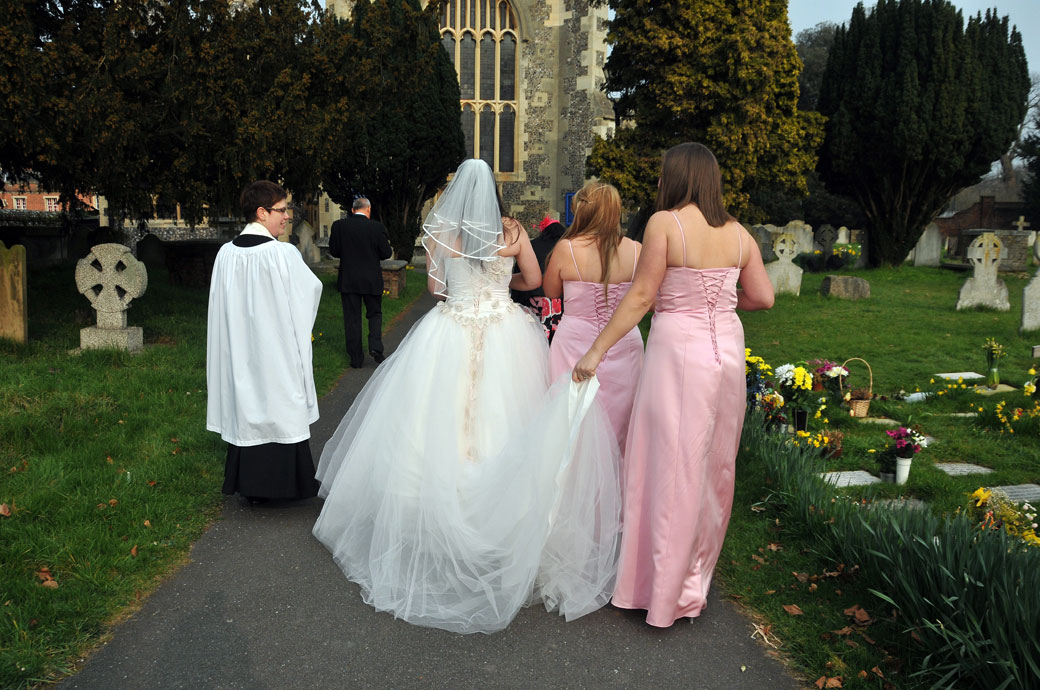 An atmospheric wedding picture of the Bride, Bridesmaids and Vicar walking down the path towards St Mary's Church Beddington Surrey