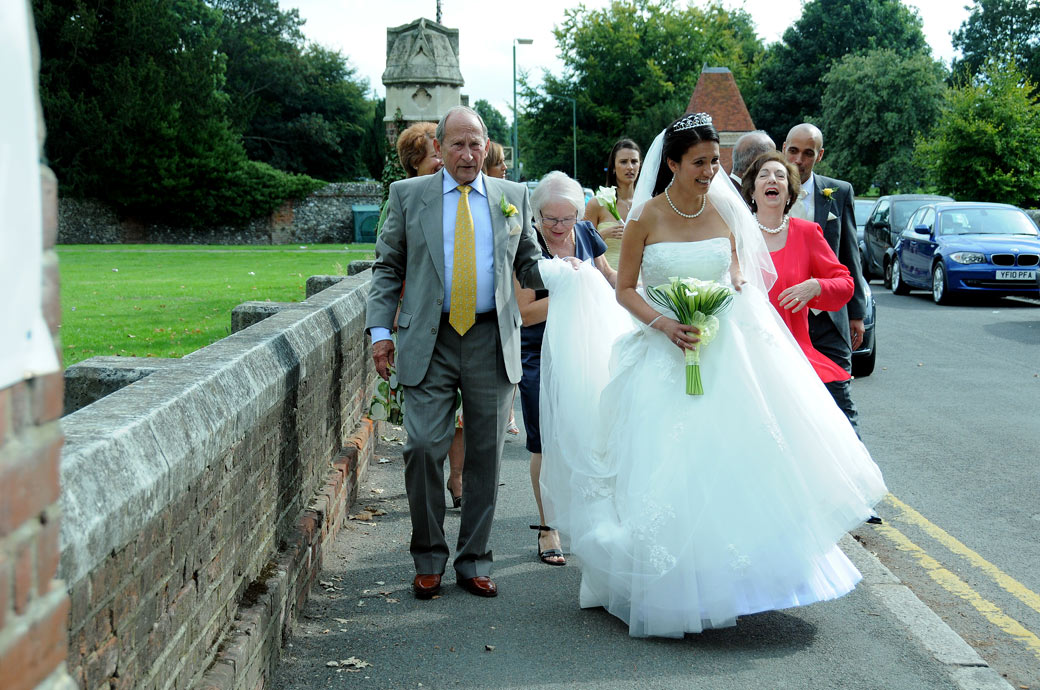 Bride and family walking along the pavement wedding photo taken as they go from St Mary's Church Beddington to Carew Manor Surrey wedding venue