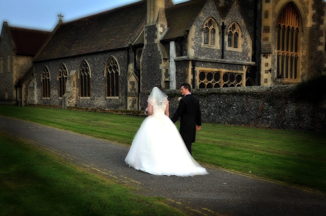 A lovely wedding photograph of the Bride and Groom walking up to Carew Manor alongside Surrey wedding venue St Mary's Church Beddington