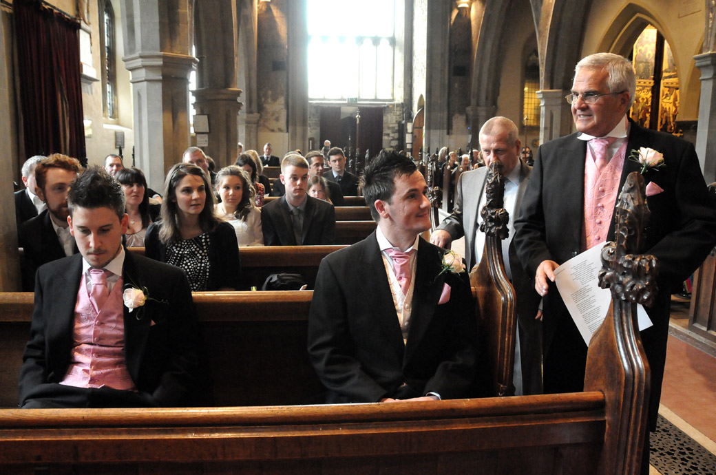 Groom and Best Man sitting in the pews waiting and contemplating wedding photo captured at St Mary's Church Beddington Surrey