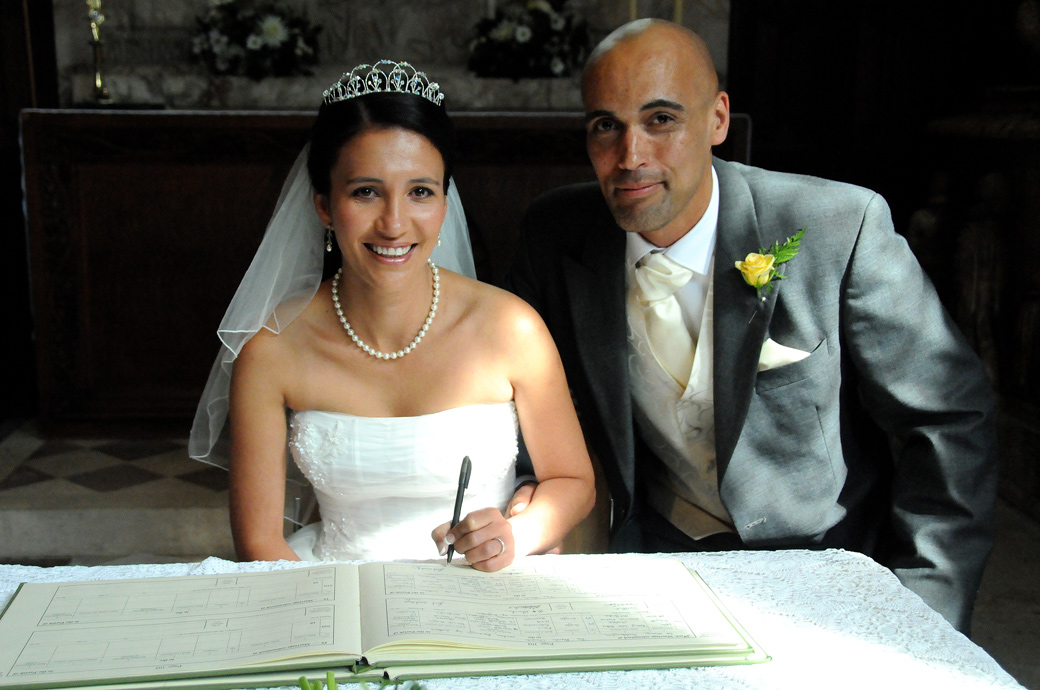 A happy Bride and Groom signing the register wedding photograph taken at the Surrey wedding venue of St Mary's Church Beddington