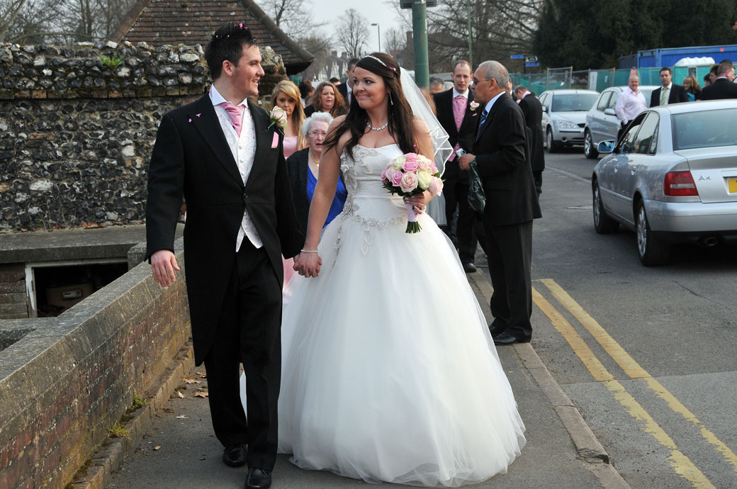 An intimate newly-weds look and acknowledgement moment wedding photo captured on the path of St Mary's Church Beddington to Carew Manor nextdoor