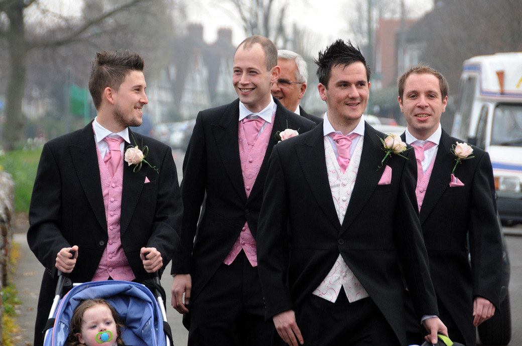 Smiling Groom and Groomsmen in pink wedding photograph taken as they arrive at the Surrey wedding venue of St Mary's Church Beddington