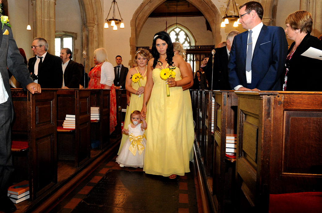 Bridesmaids all in yellow walking down the aisle wedding picture captured at St Mary's Church Oxted by Surrey Lane wedding photography