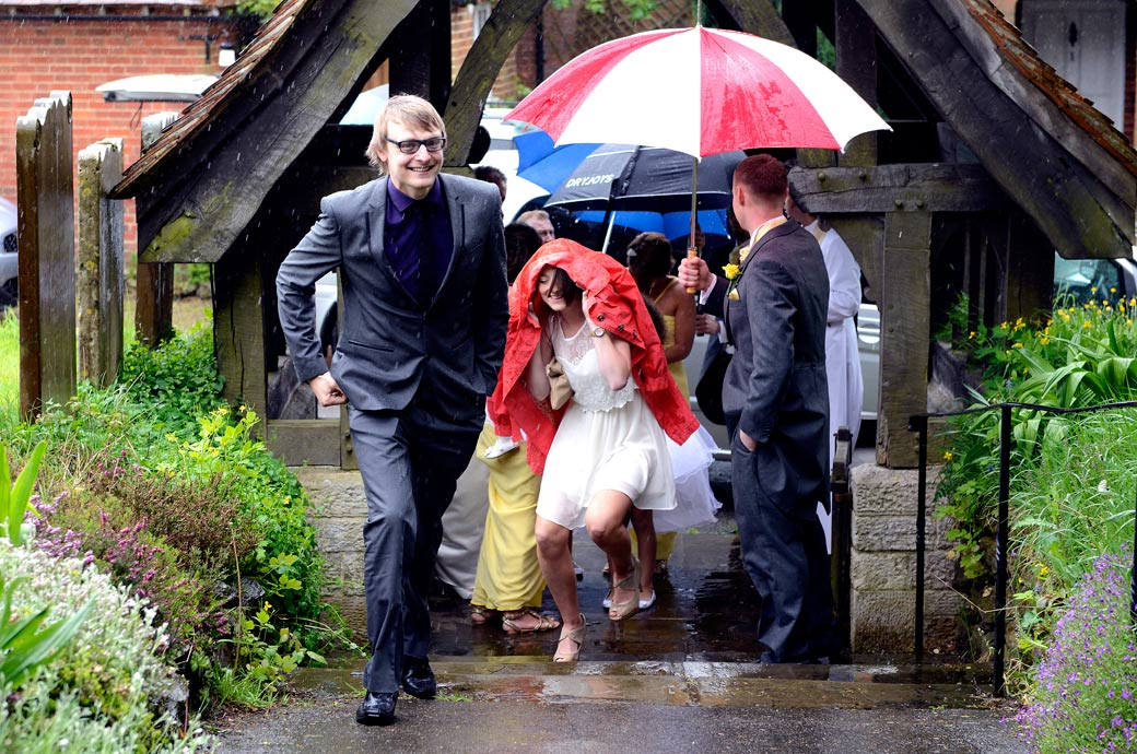 Wedding guests dodging the rain in this fun wedding photograph taken on the path from the lychgate to Surrey wedding venue St Mary's Church Oxted