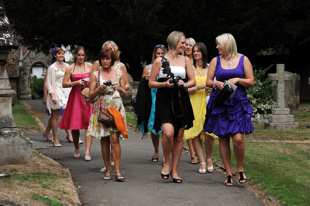 Lovely colourful chatting ladies with cameras wedding picture taken outside Surrey wedding venue St Michael's Church Betchworth