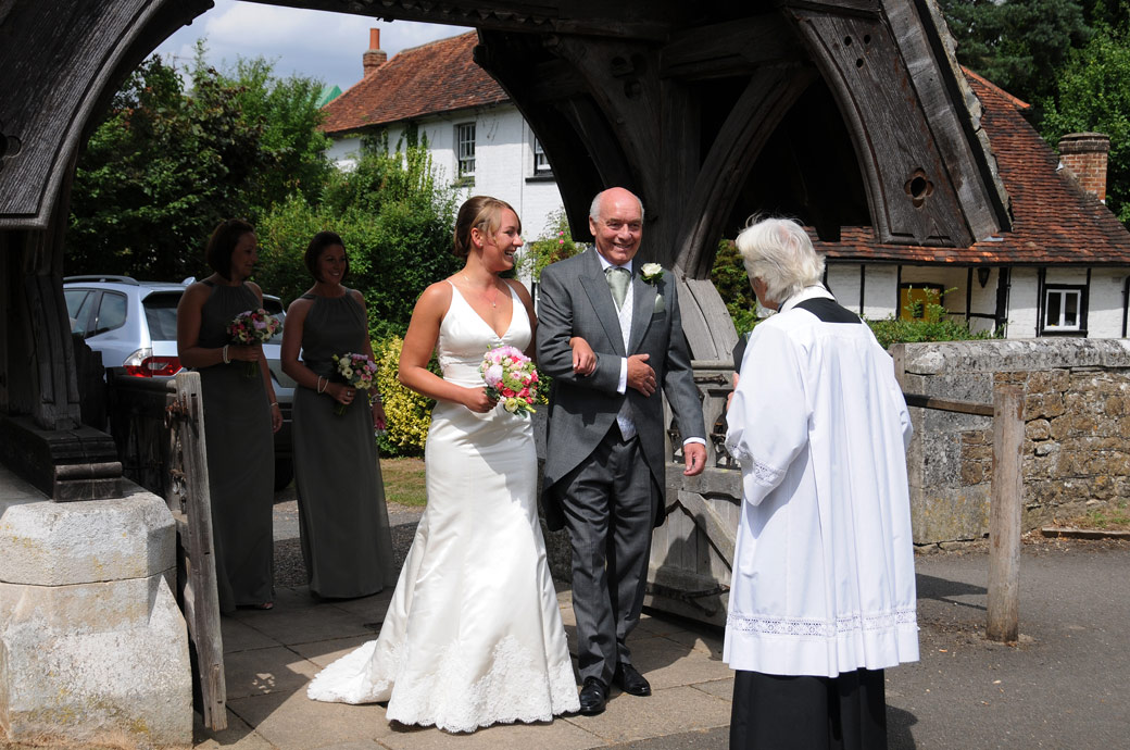 The priest greeting the Father and Bride wedding photograph taken by Surrey Lane wedding photography at Surrey wedding venue St Michael's Betchworth