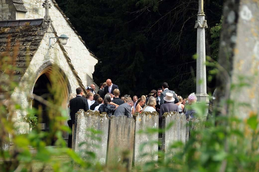 An atmospheric distant spyhole wedding picture of all the guests gathered  outside St Michael's Betchworth Surrey wedding venue