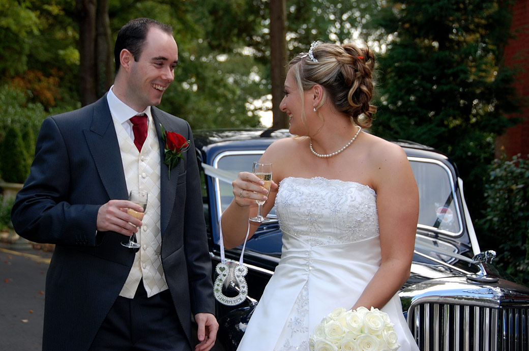 Bride and Groom share a joke and laughter over a glass of champagne in this wedding photo captured at Stanhill Court Hotel by Surrey Lane wedding photography
