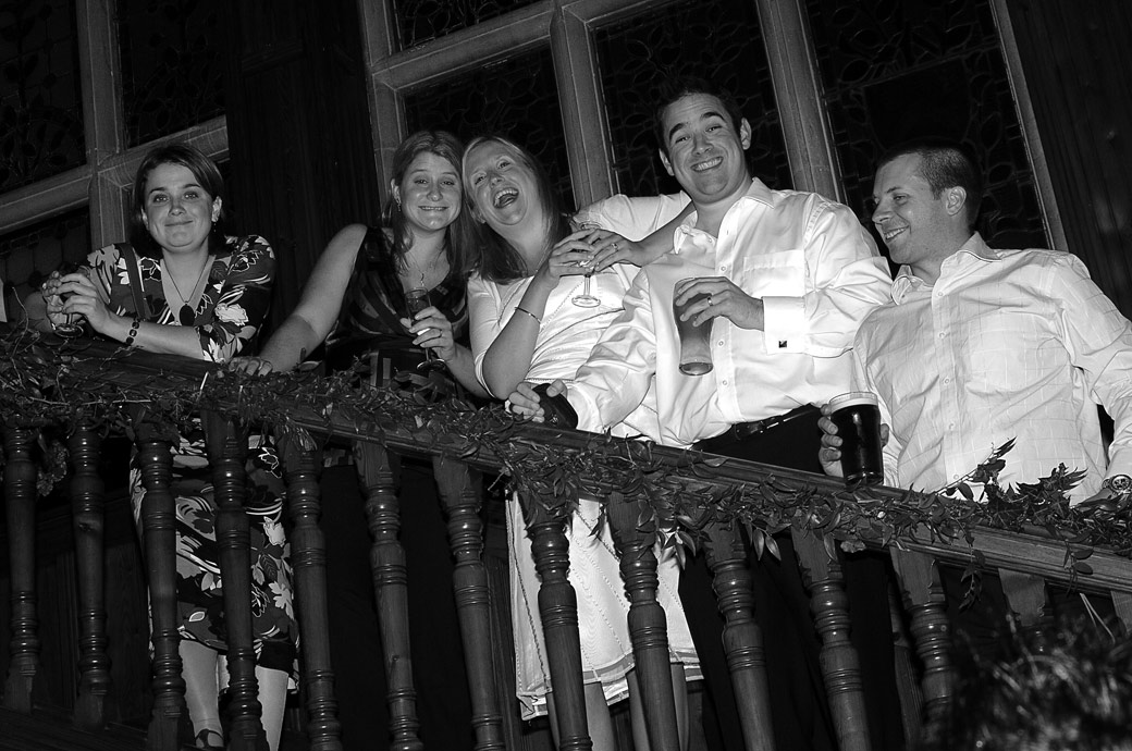 Smiles, fun and laughter for guests up on the main staircase in this wedding photo taken by Surrey Lane wedding photographers at Stanhill Court Hotel