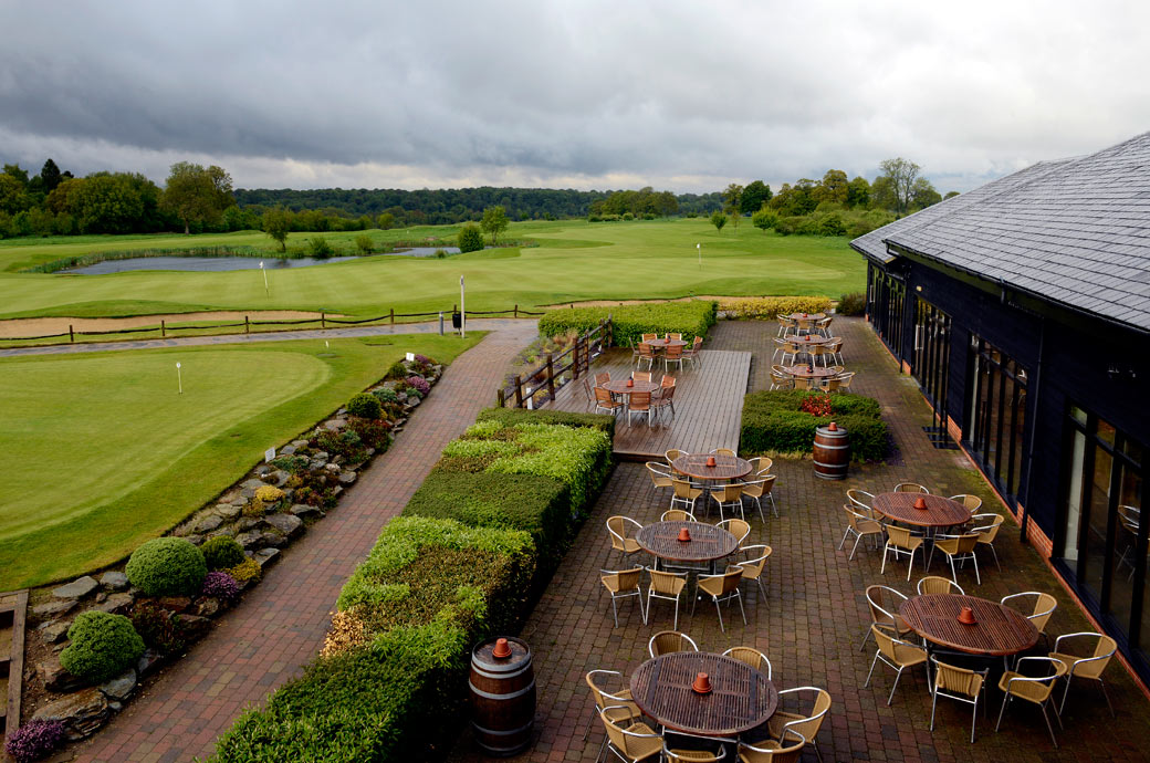 An aerial wedding photo taken of the greens and lake beyond an empty wet patio at the tranquil and picturesque Surrey wedding venue Surrey Downs Golf Club