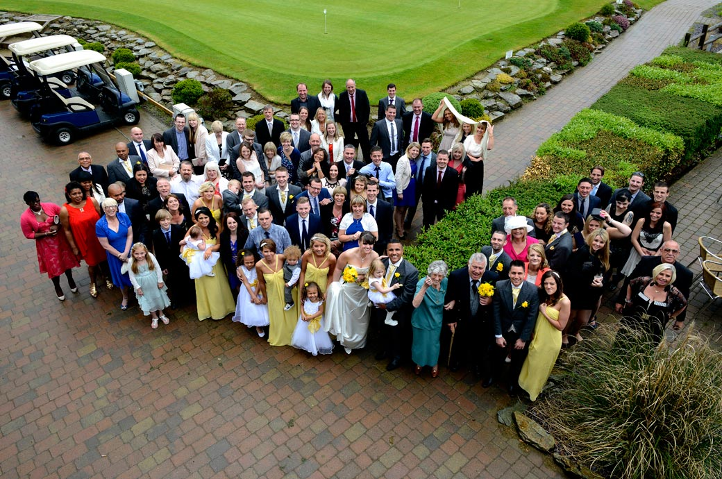 Quickly grabbed everyone group wedding photo taken from the balcony on a very wet and windy day by Surrey lane wedding photographers at Surrey Downs Golf Club